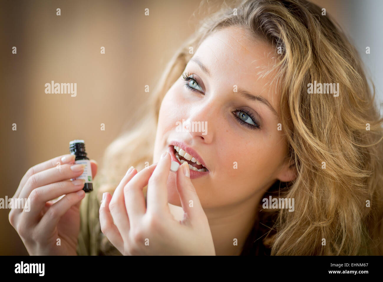 Woman applying essential oil on a neutral pill. - Stock Image