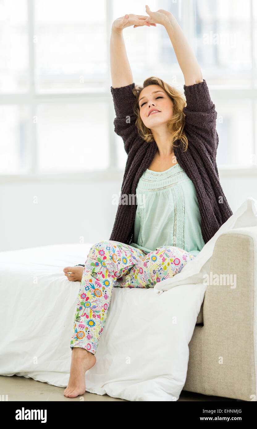 Woman waking up and stretching in bed. - Stock Image