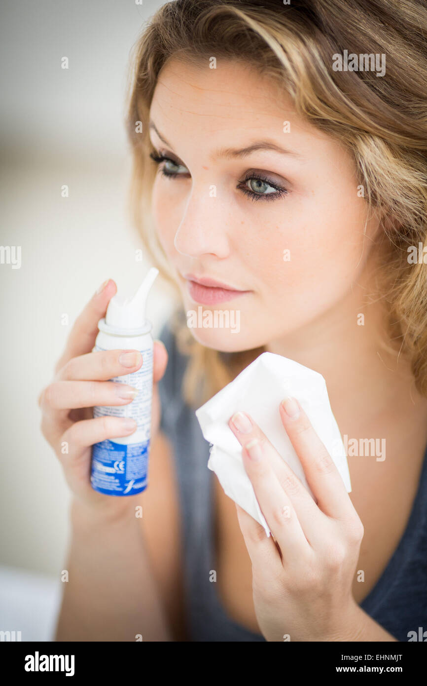 Woman using a sterile sea water spray. - Stock Image