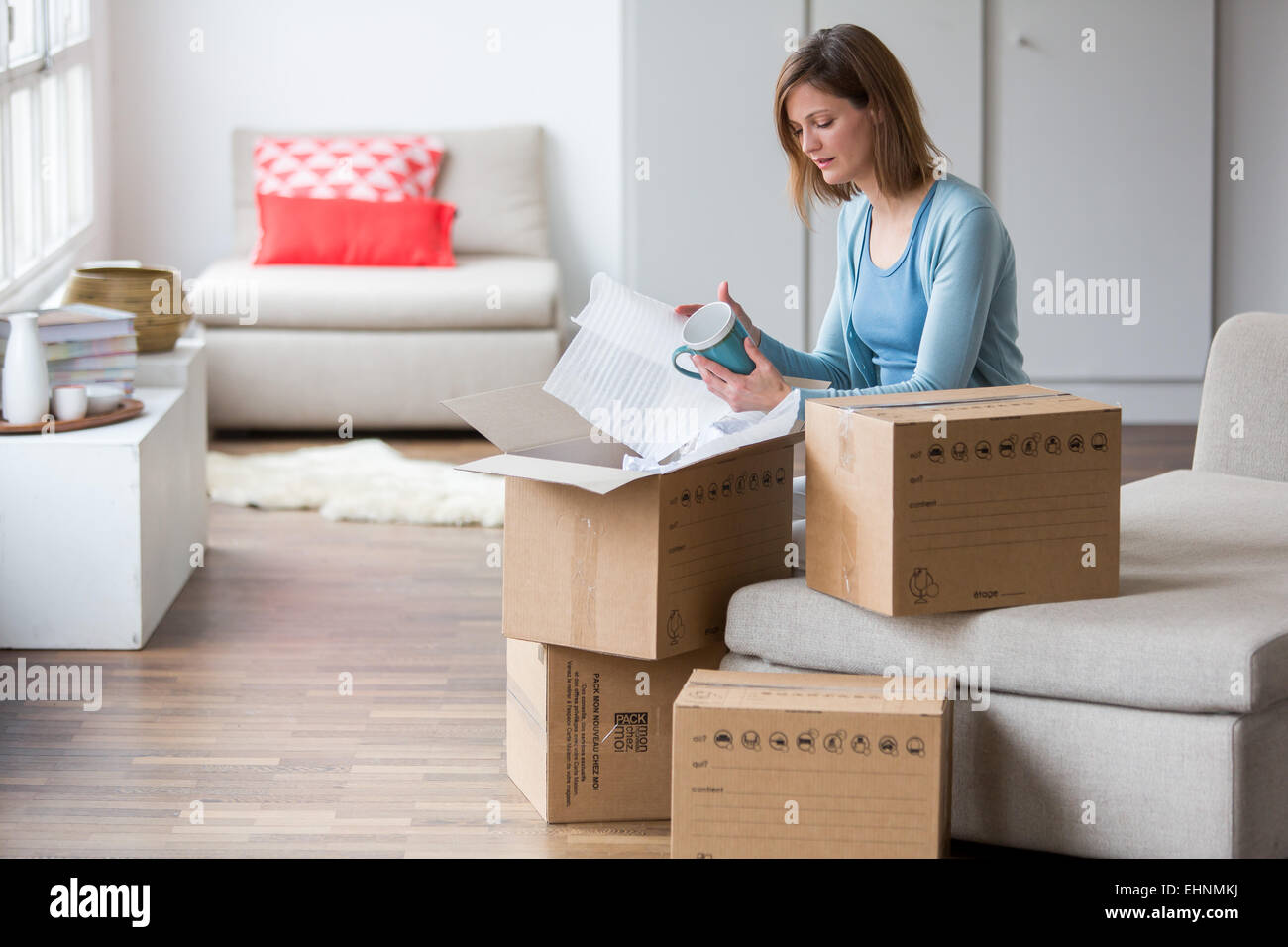 Woman carrying moving boxes in her new home. - Stock Image