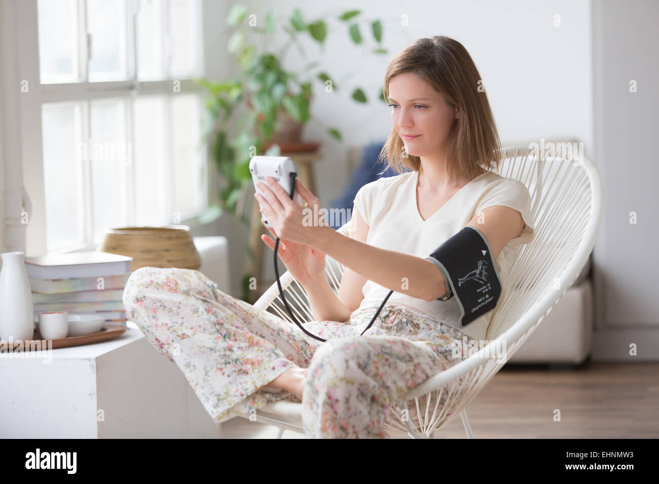 Woman taking her blood pressure with a portable blood pressure monitor. - Stock Image