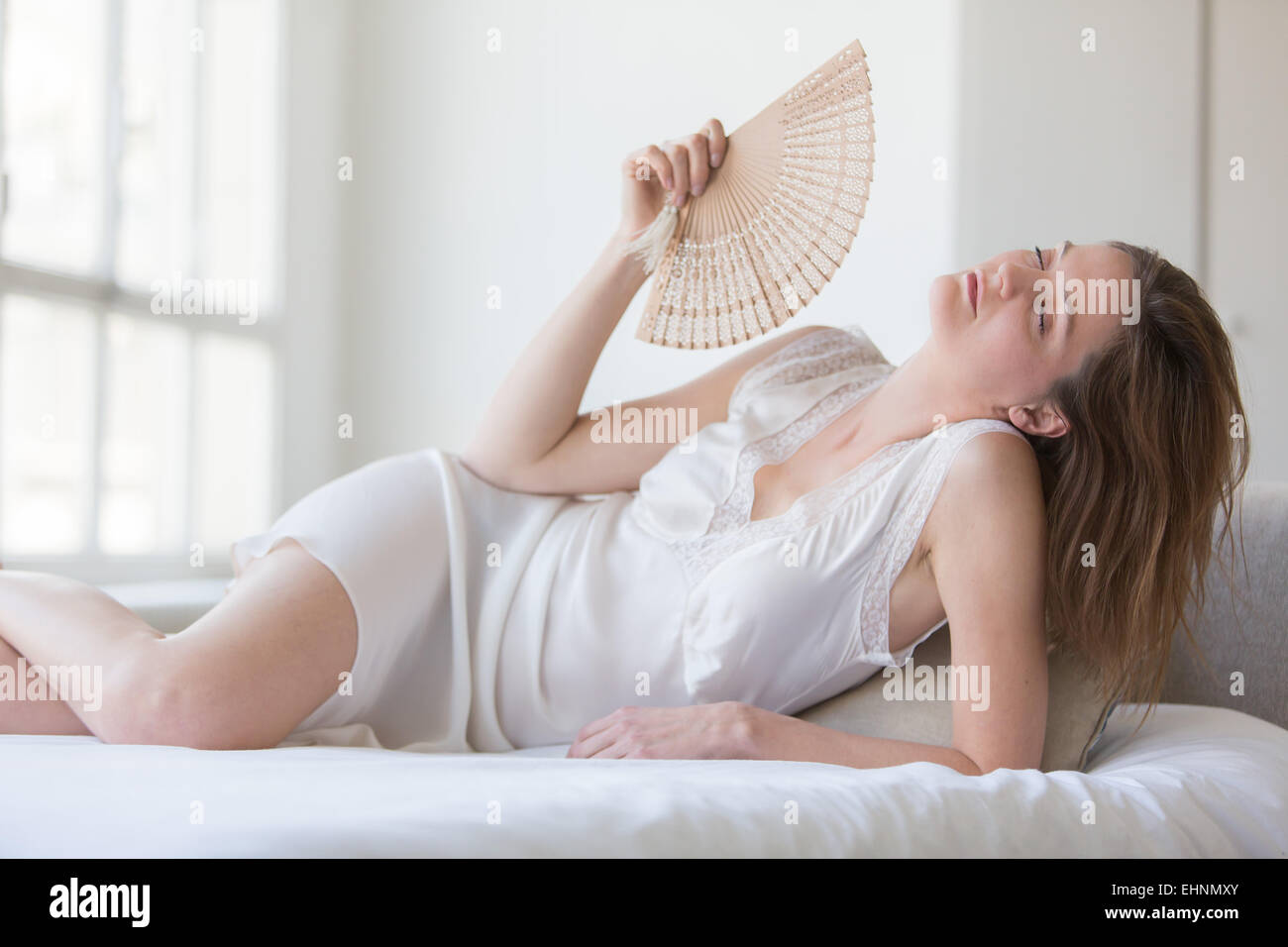 Woman cooling her face with a fan. - Stock Image