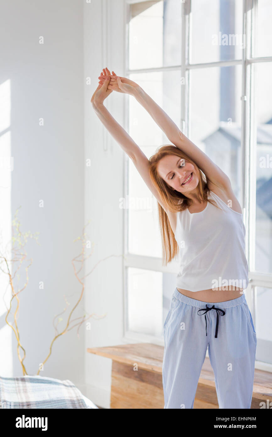 Woman waking up and stretching. - Stock Image