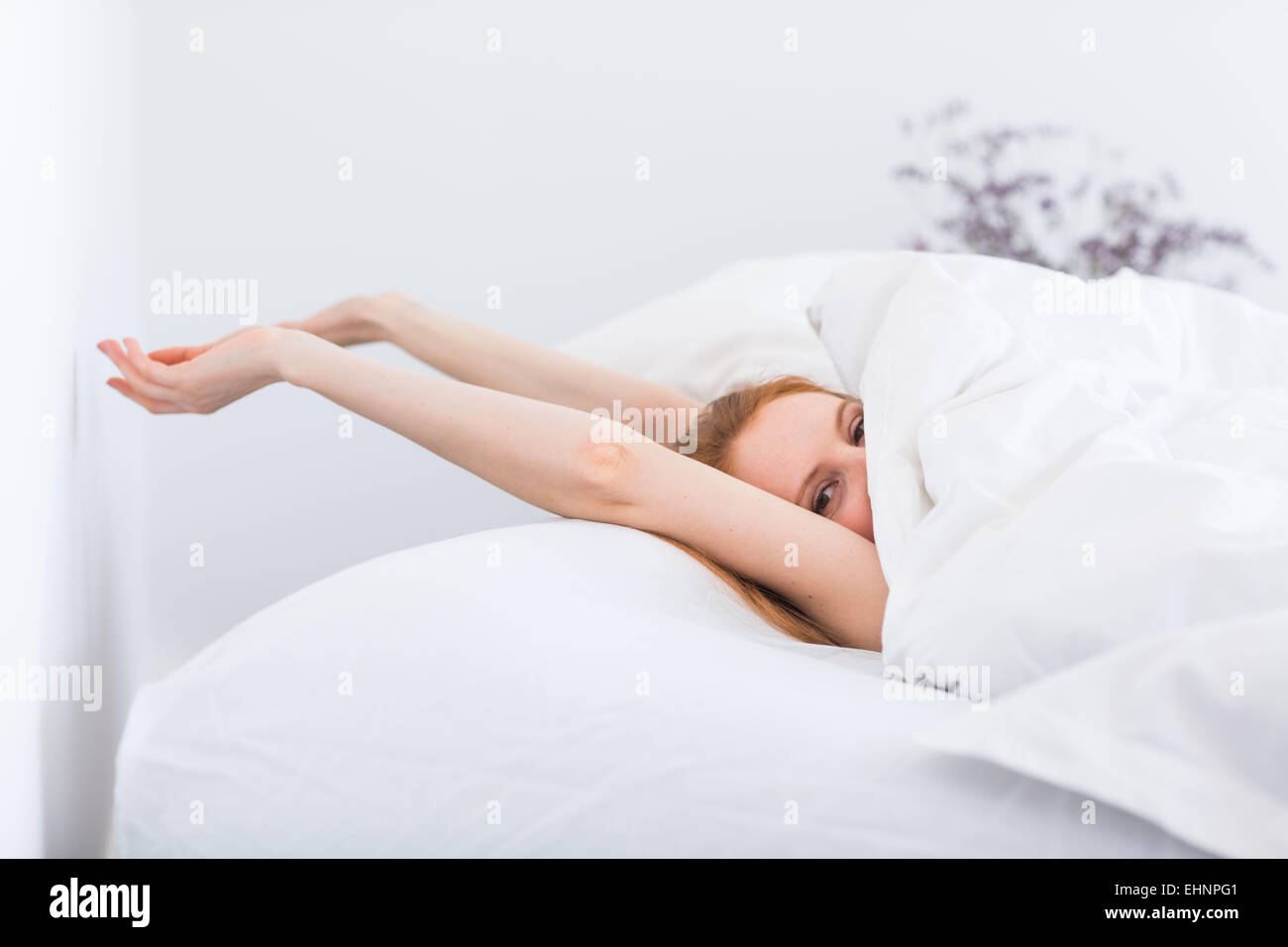 Woman waking up and stretching in bed. Stock Photo