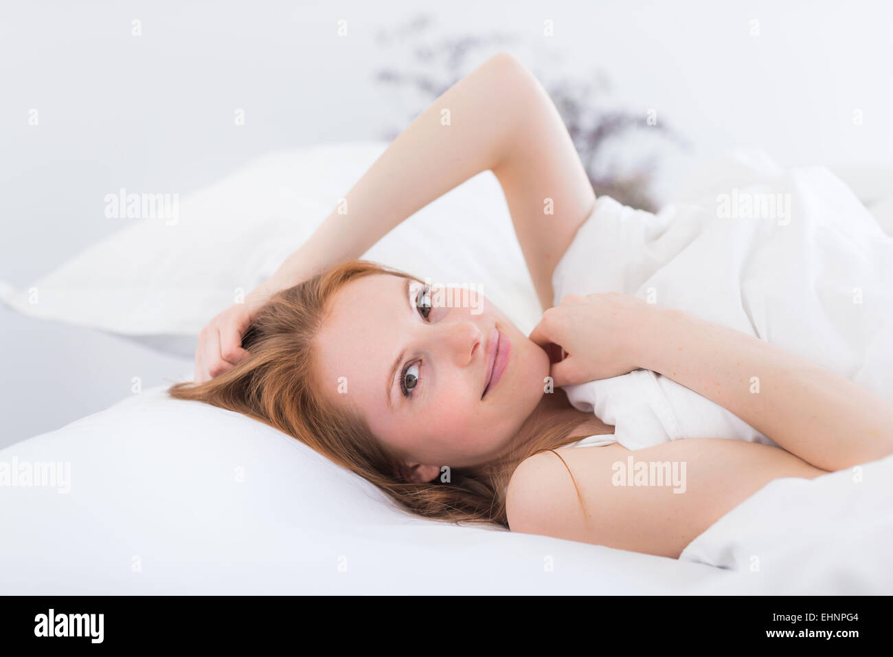 Woman laying in bed, head on pillow, smiling at camera - Stock Image