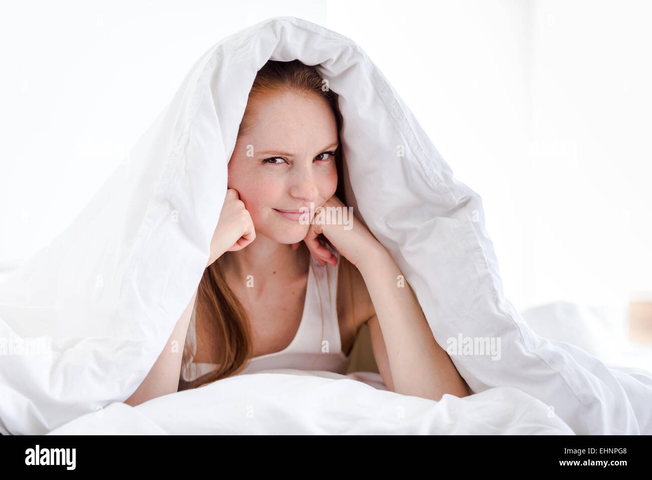 Woman sitting on bed. - Stock Image