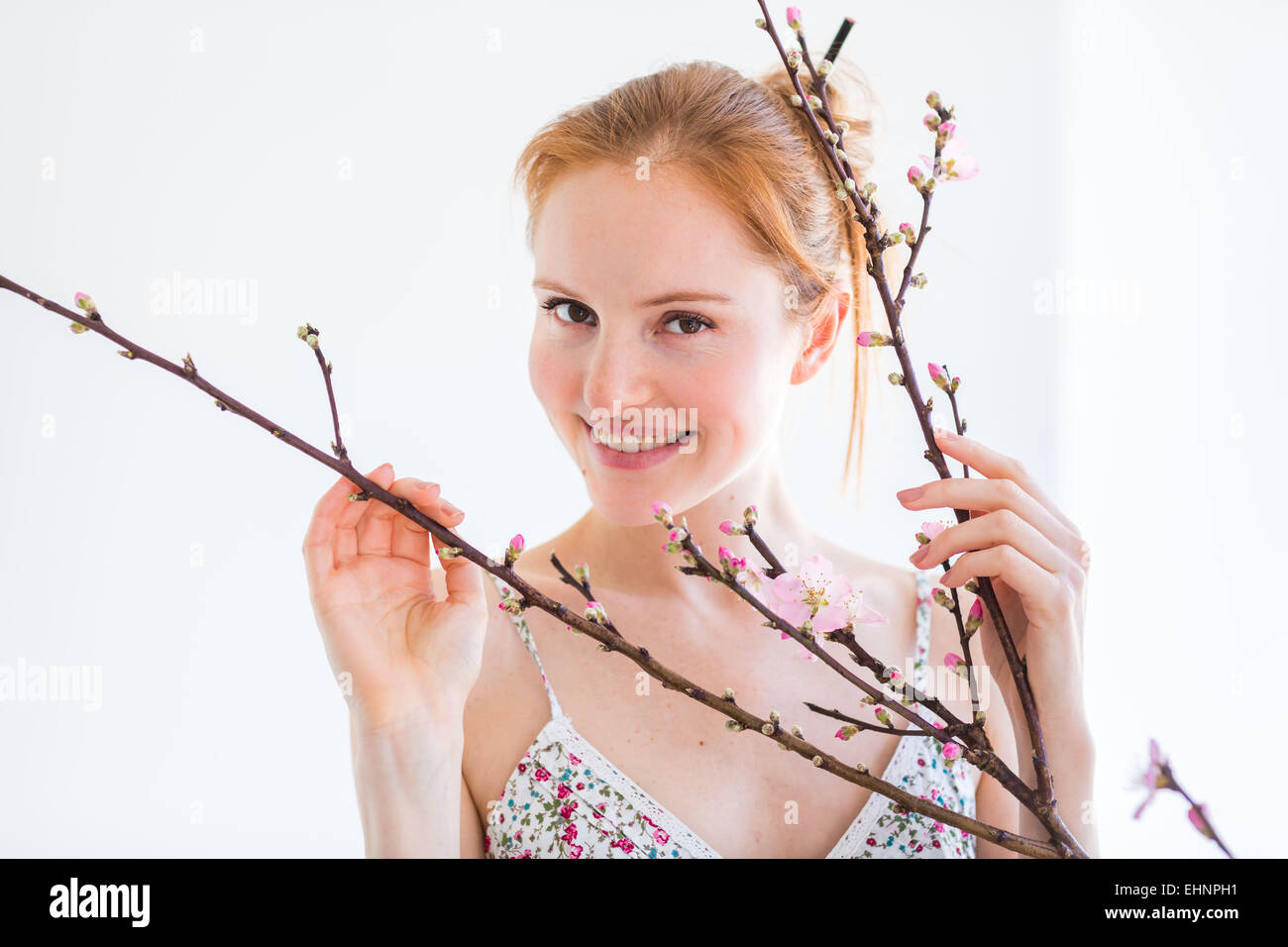 Woman in front of a blooning Prunus branch . - Stock Image
