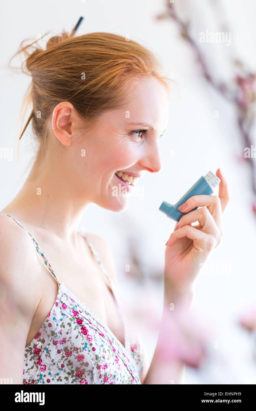 Woman using an aerosol inhaler that contains bronchodilator for the treatment of asthma. - Stock Image
