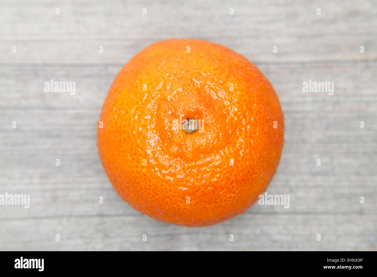 tangerine on a grey table - Stock Image