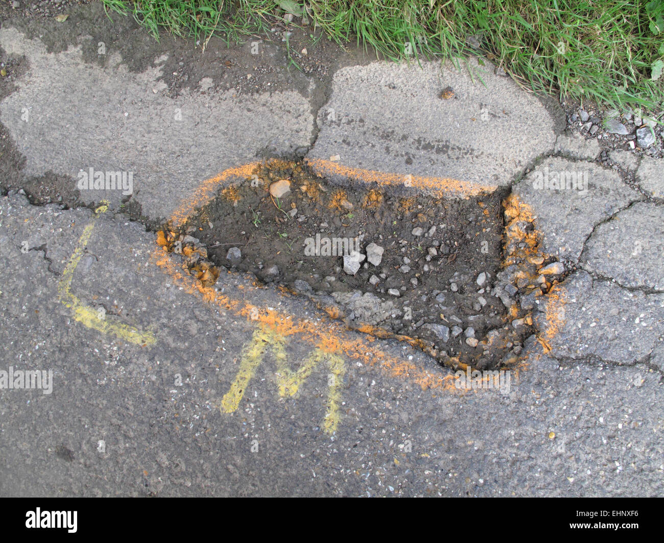 Potholes in broken tarmac country road  marked to warn cyclists of the danger, Berkshire, July - Stock Image