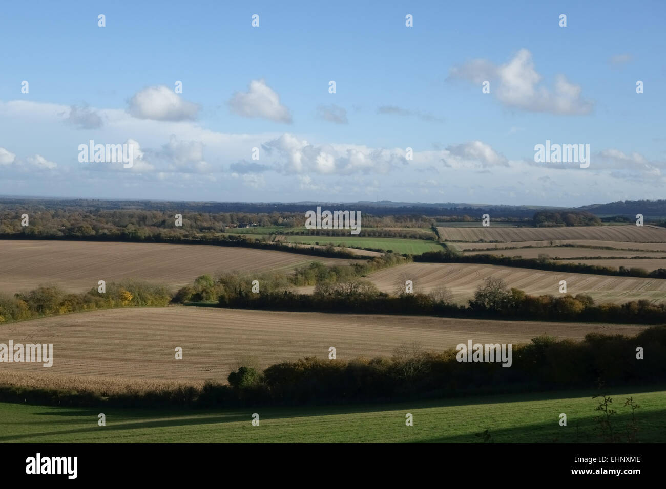View over farmland with fallow fields and hedgerows from downland in West Berkshire on a bright fine autumn day - Stock Image