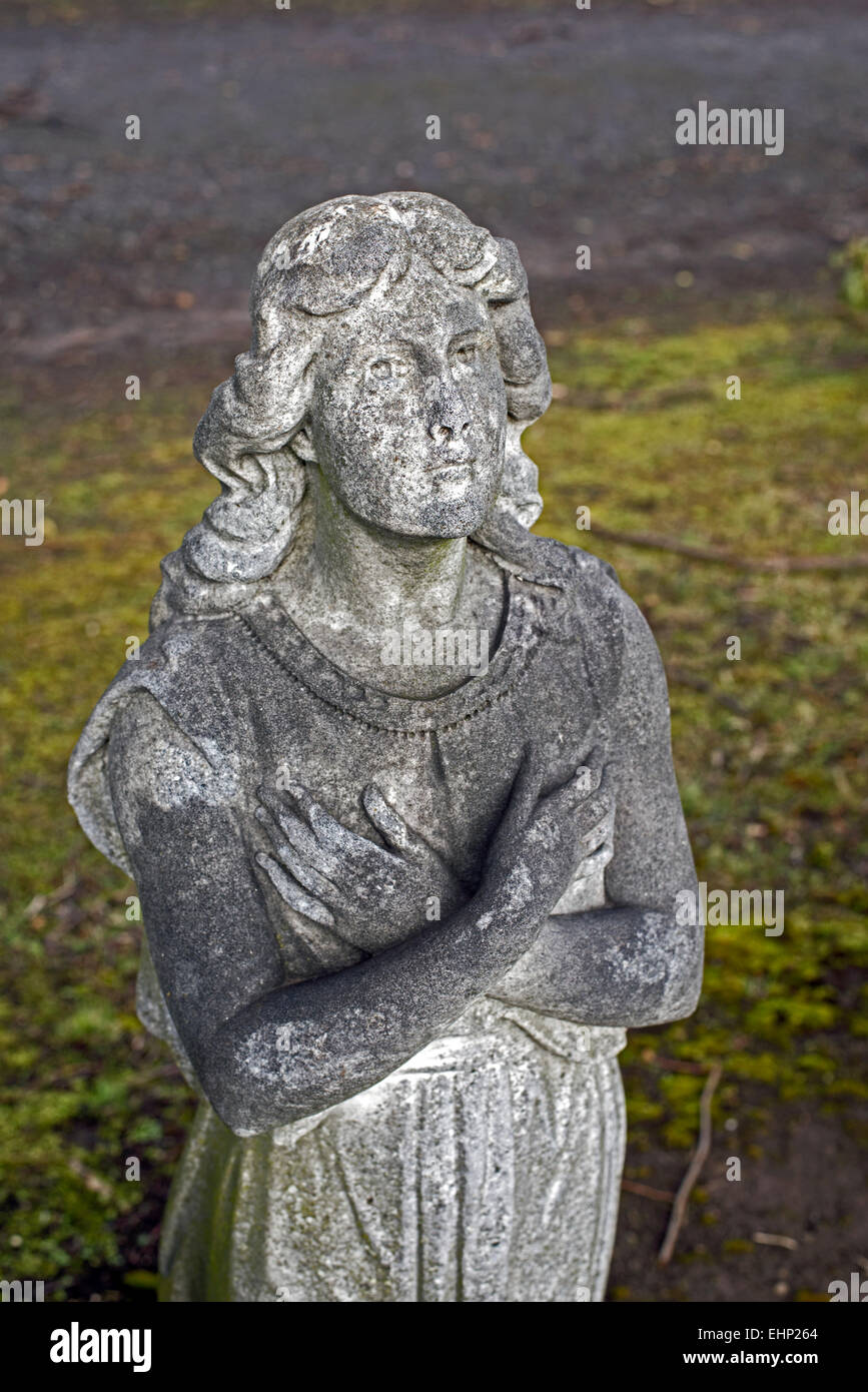 Detail from a damaged memorial in Morningside Cemetery showing the figure of a  woman with her arms folded across - Stock Image