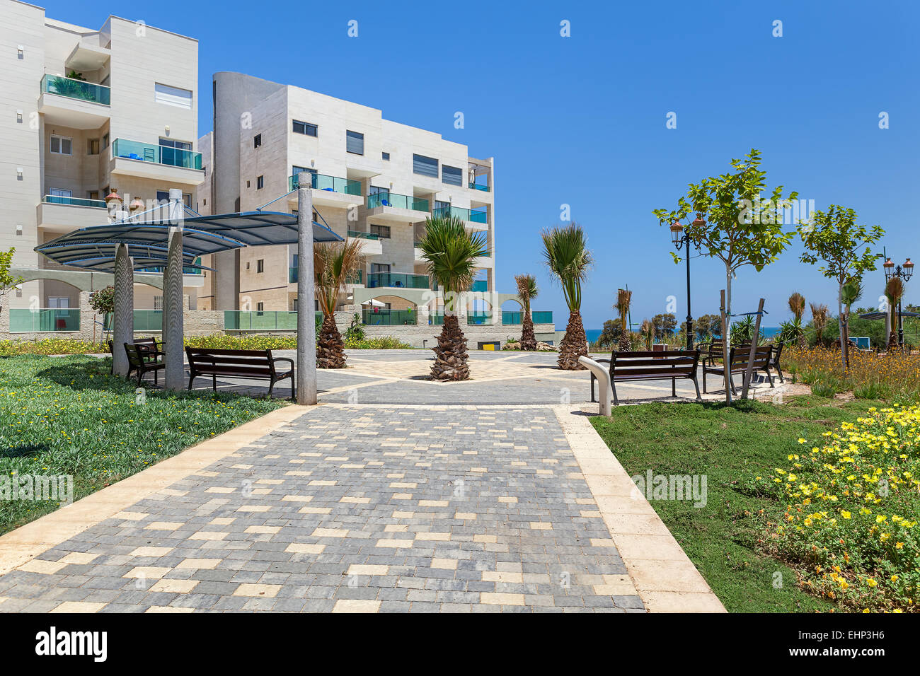 Small city square with palms and benches near complex of modern residential buildings in Ashqelon, Israel. - Stock Image
