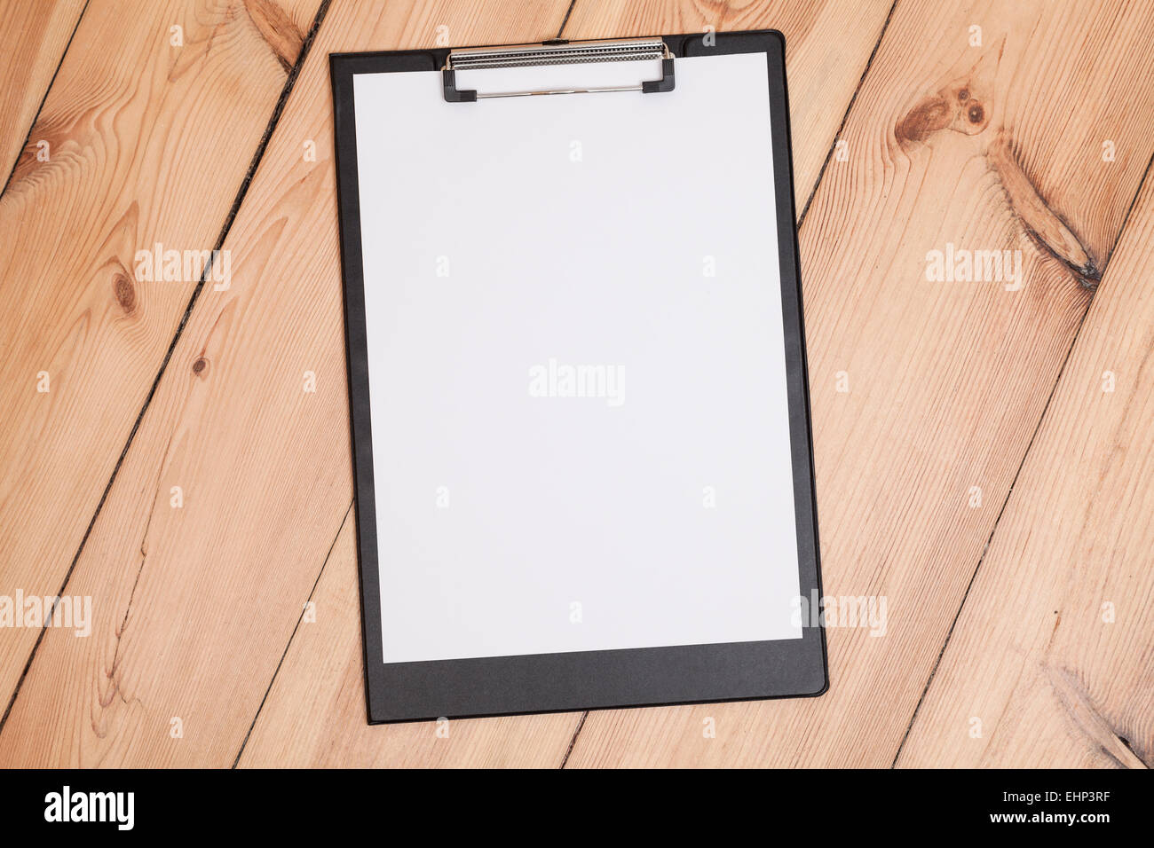 clipboard with white sheet on wooden floor - Stock Image