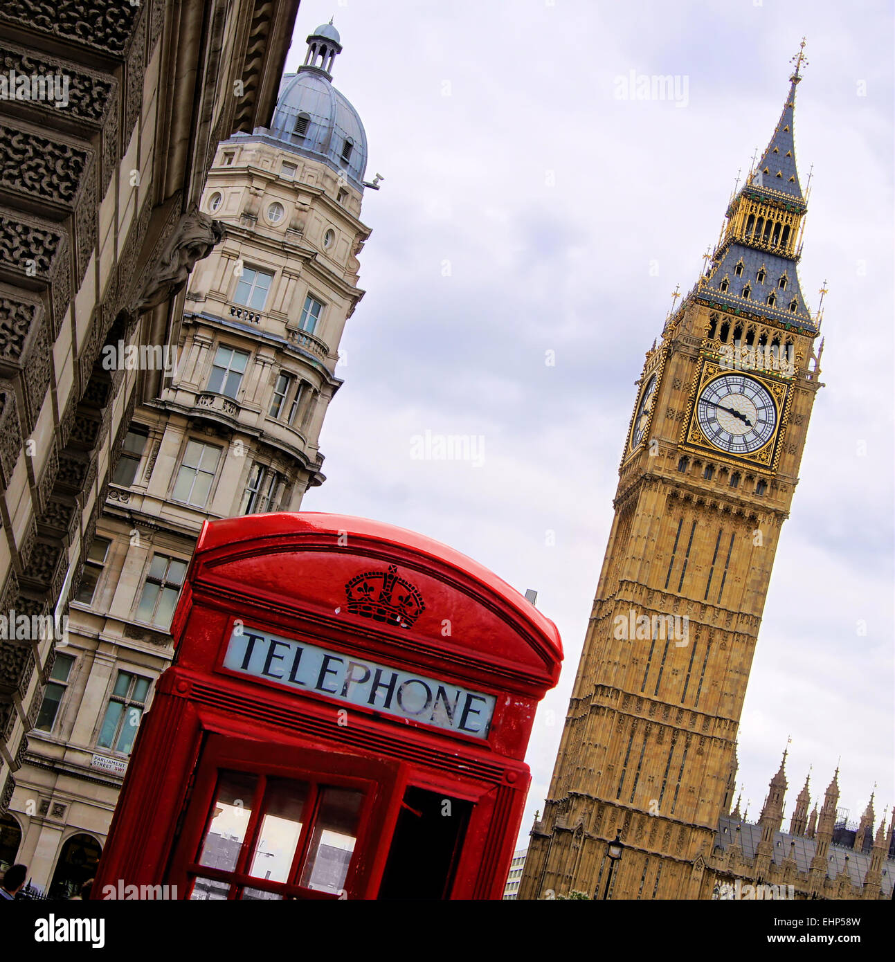 Traditional red English telephone box with the Tower of Big Ben in background - Stock Image