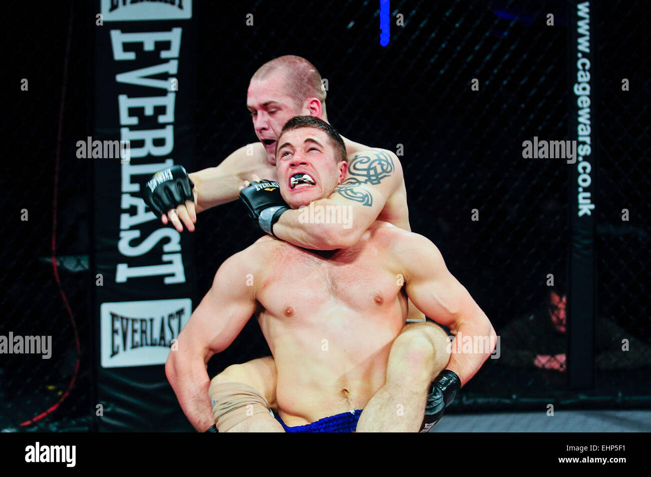 MMA cage fighter puts his opponent into a choke hold with his arm around the neck. - Stock Image