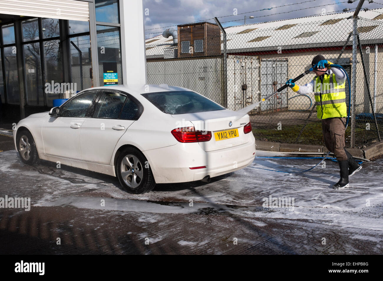 Car being washed in a modern styled car wash, using high pressure water hoses, Glasgow, Scotland, UK - Stock Image