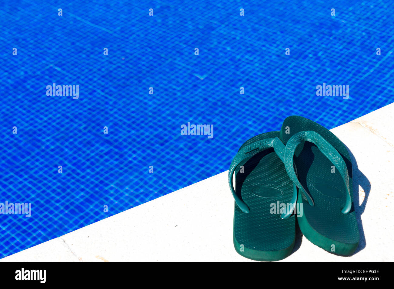 Flip-flops by the swimming pool - Stock Image