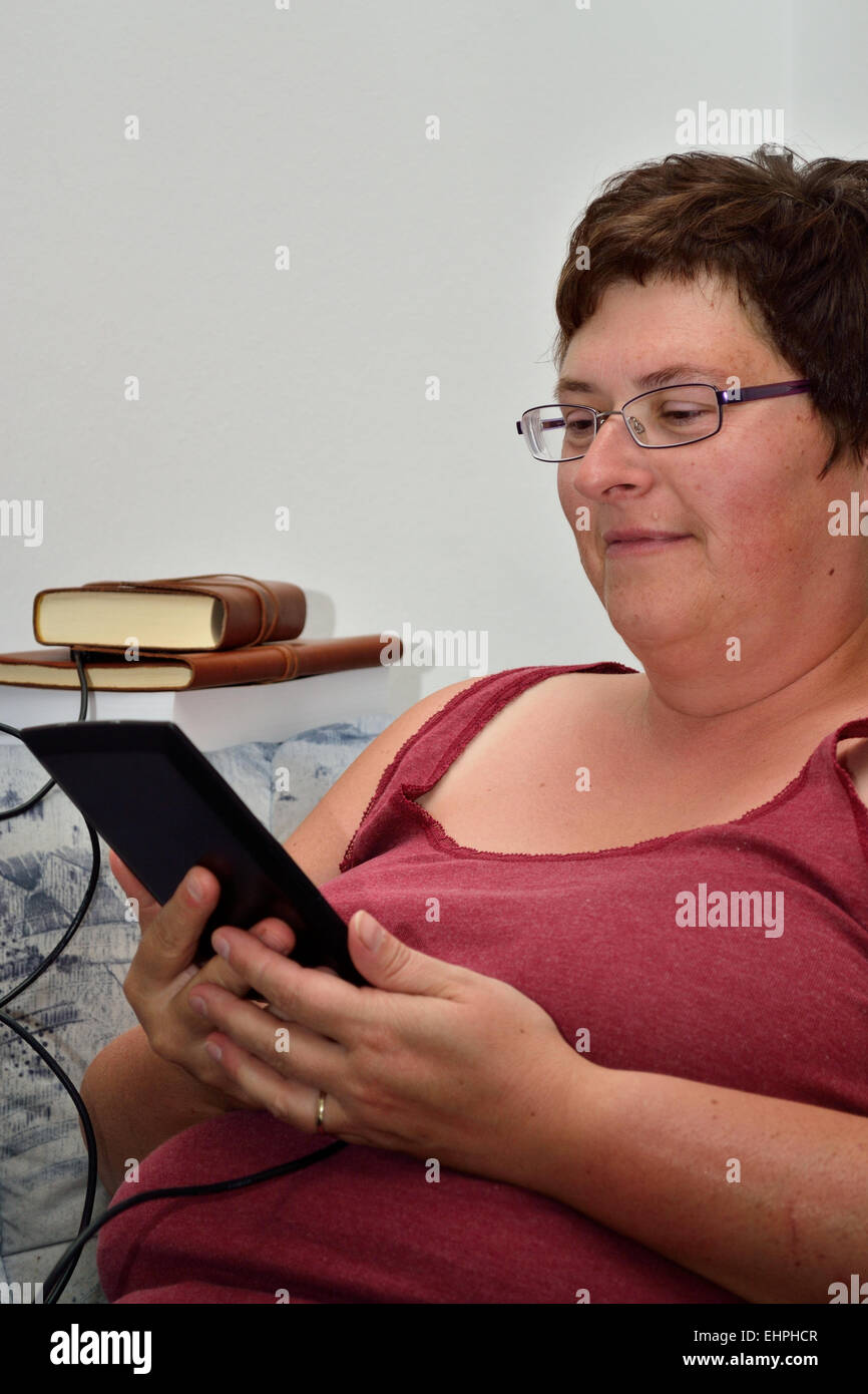 Woman reading in eBook - Stock Image