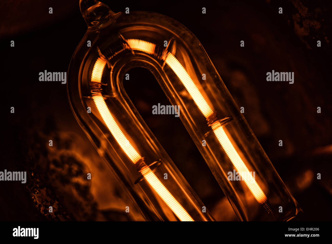 glowing filament of a 1000 quartz halogen bulb with flaked metal and heat damage to the reflector and heat dispenser - Stock Image