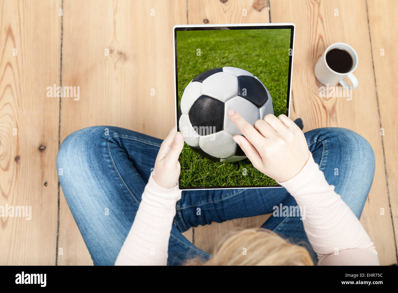 woman pointing on soccer ball on tablet - Stock Image