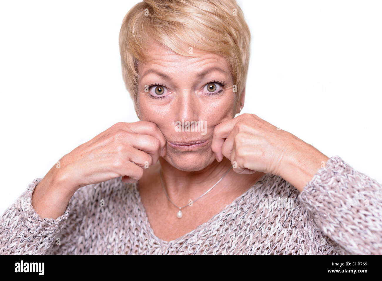 Attractive middle-aged woman with short blond hair trying to reverse the signs of aging by pulling on her cheeks - Stock Image