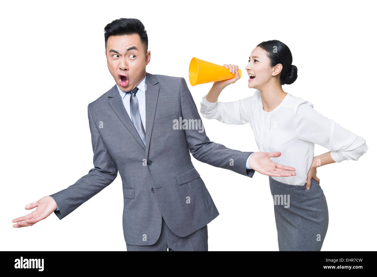 Young businesswoman shouting at businessman through megaphone - Stock Image