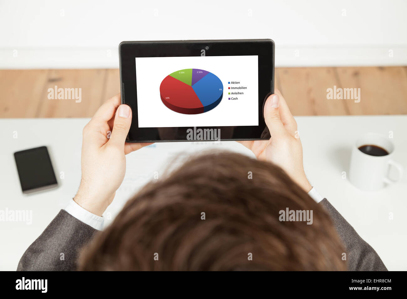 businessman looking at portfolio on tablet - Stock Image
