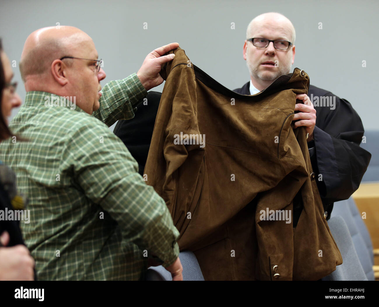 Siegen, Germany. 17th Mar, 2015. A 32-year old woman is covered with a jacket by her lawyer Daniel Nierenz (r) and - Stock Image