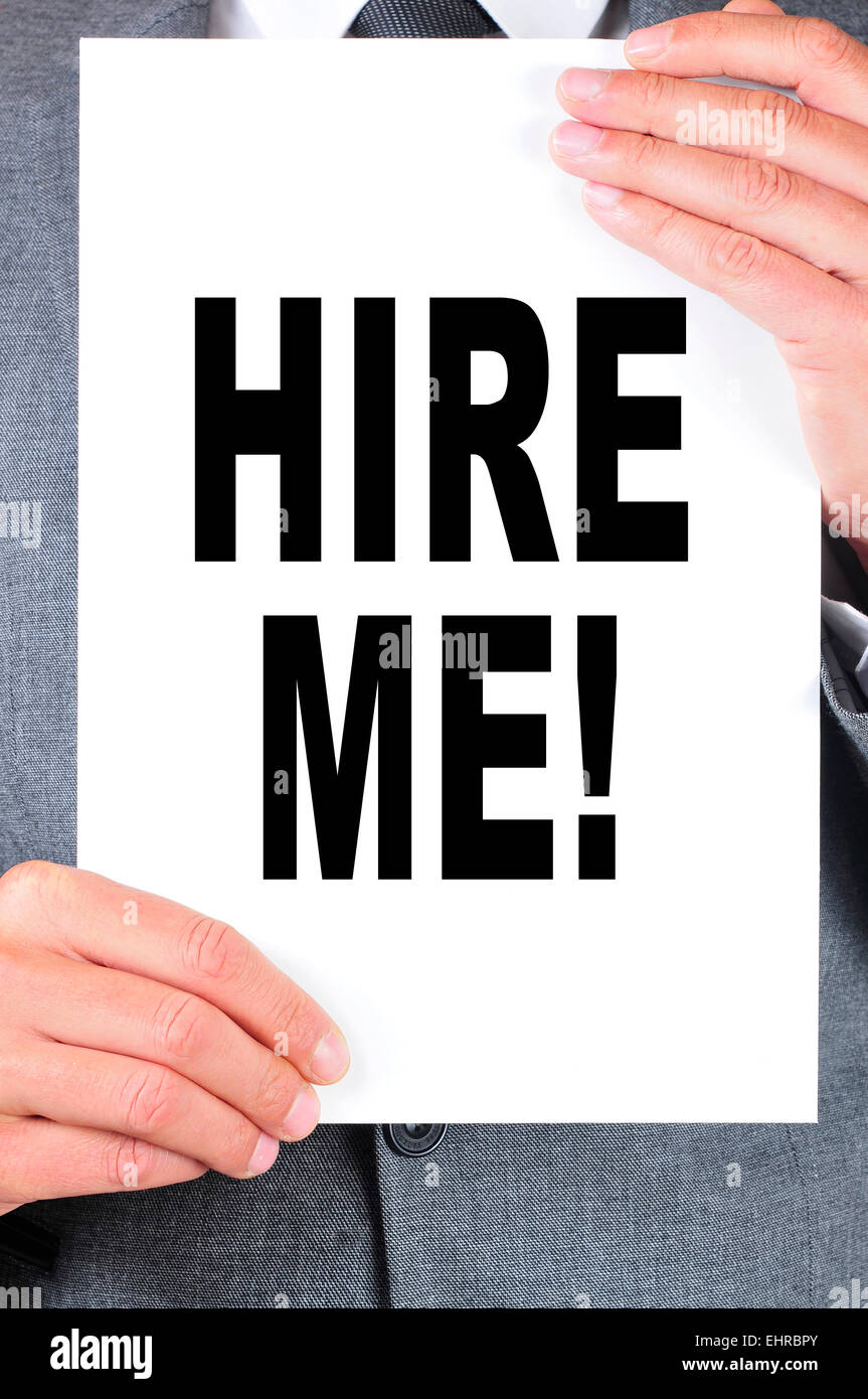 a man wearing a suit holding a signboard with the text hire me written on it - Stock Image