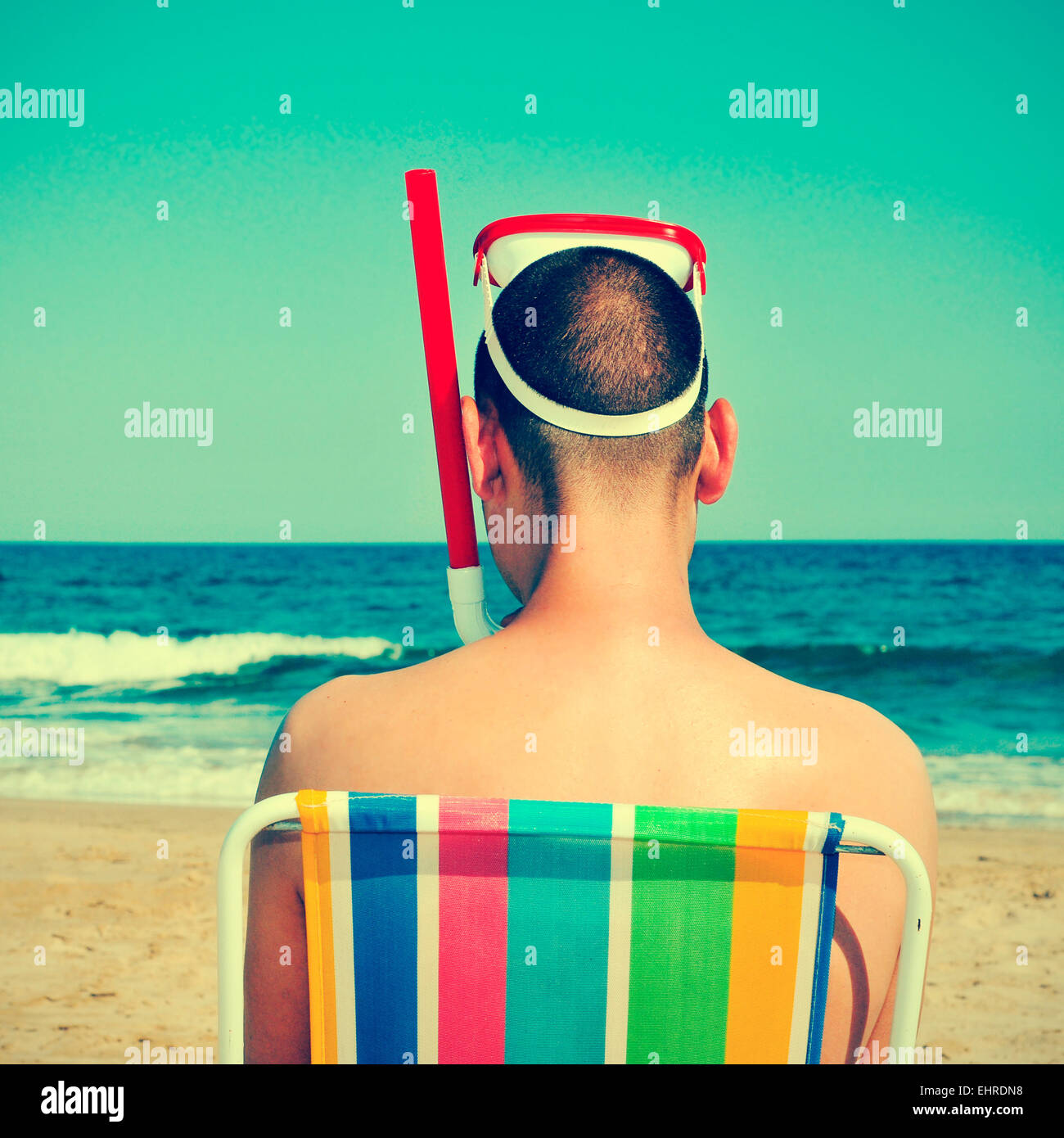 picture from the back of a man wearing a diving mask and a snorkel seated in a deckchair on the beach, with a retro - Stock Image