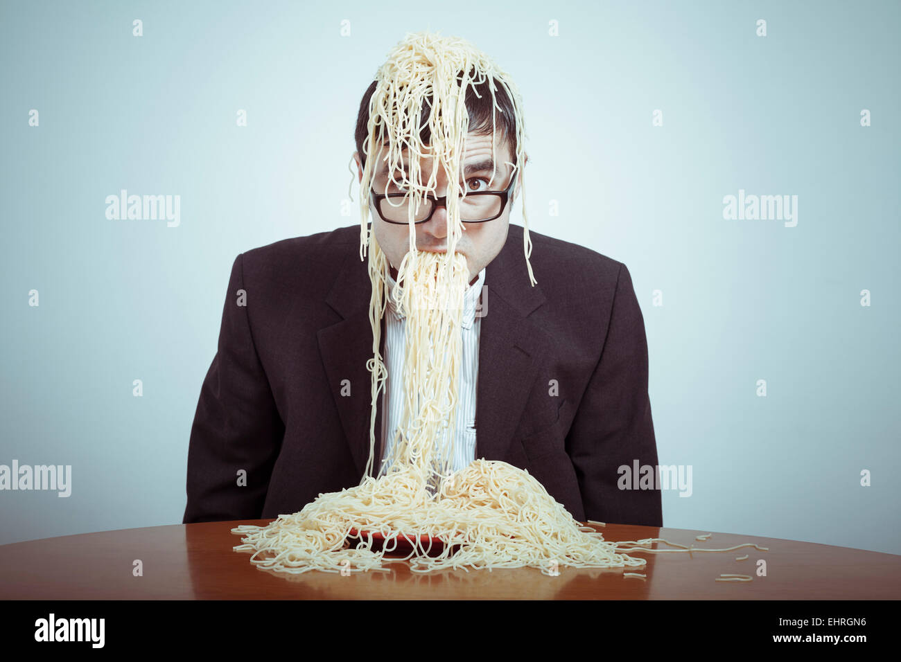 Overeating and consumerism concept. Nasty businessman eating pasta. - Stock Image