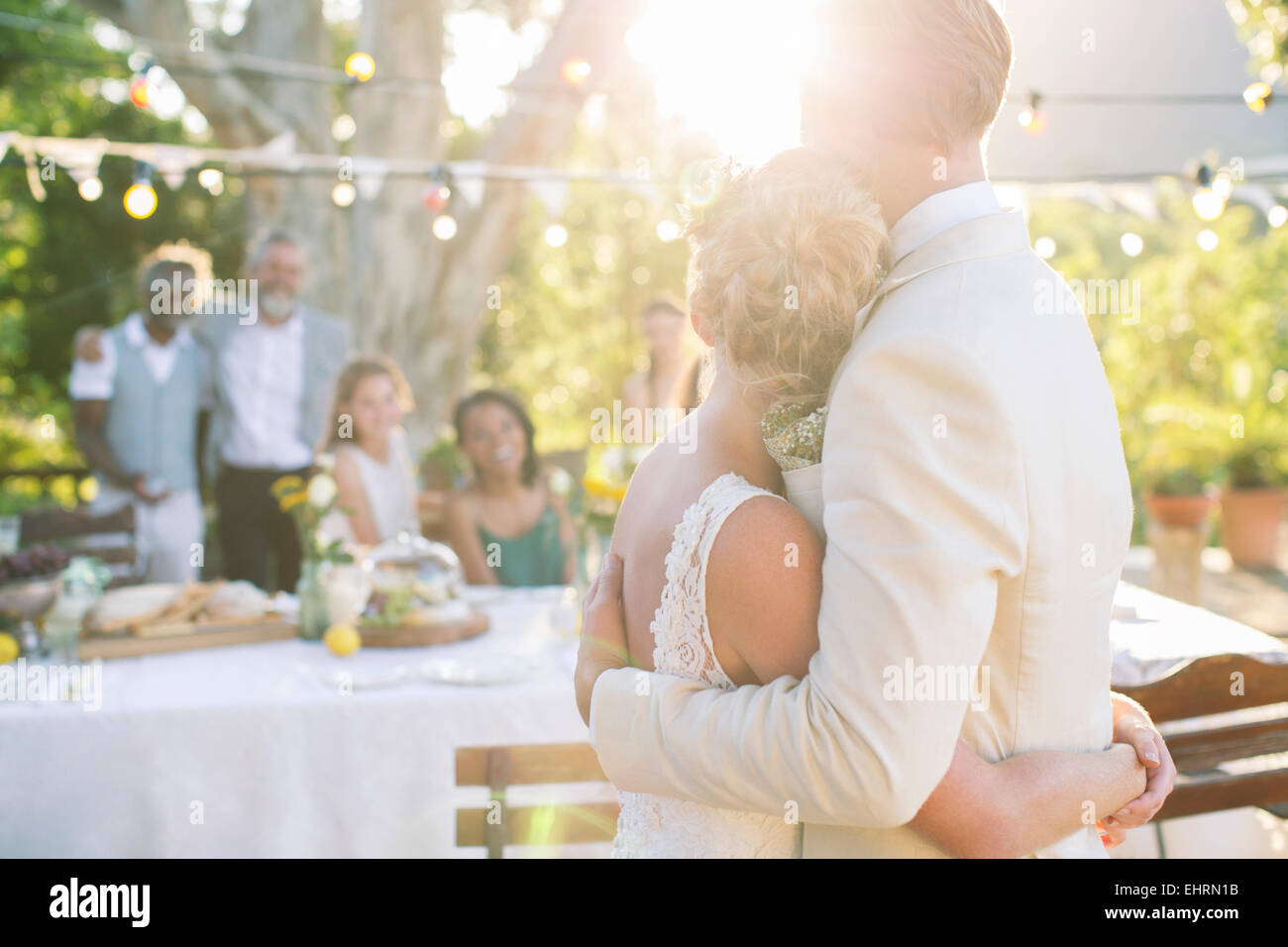 Young couple embracing in garden during wedding reception - Stock Image