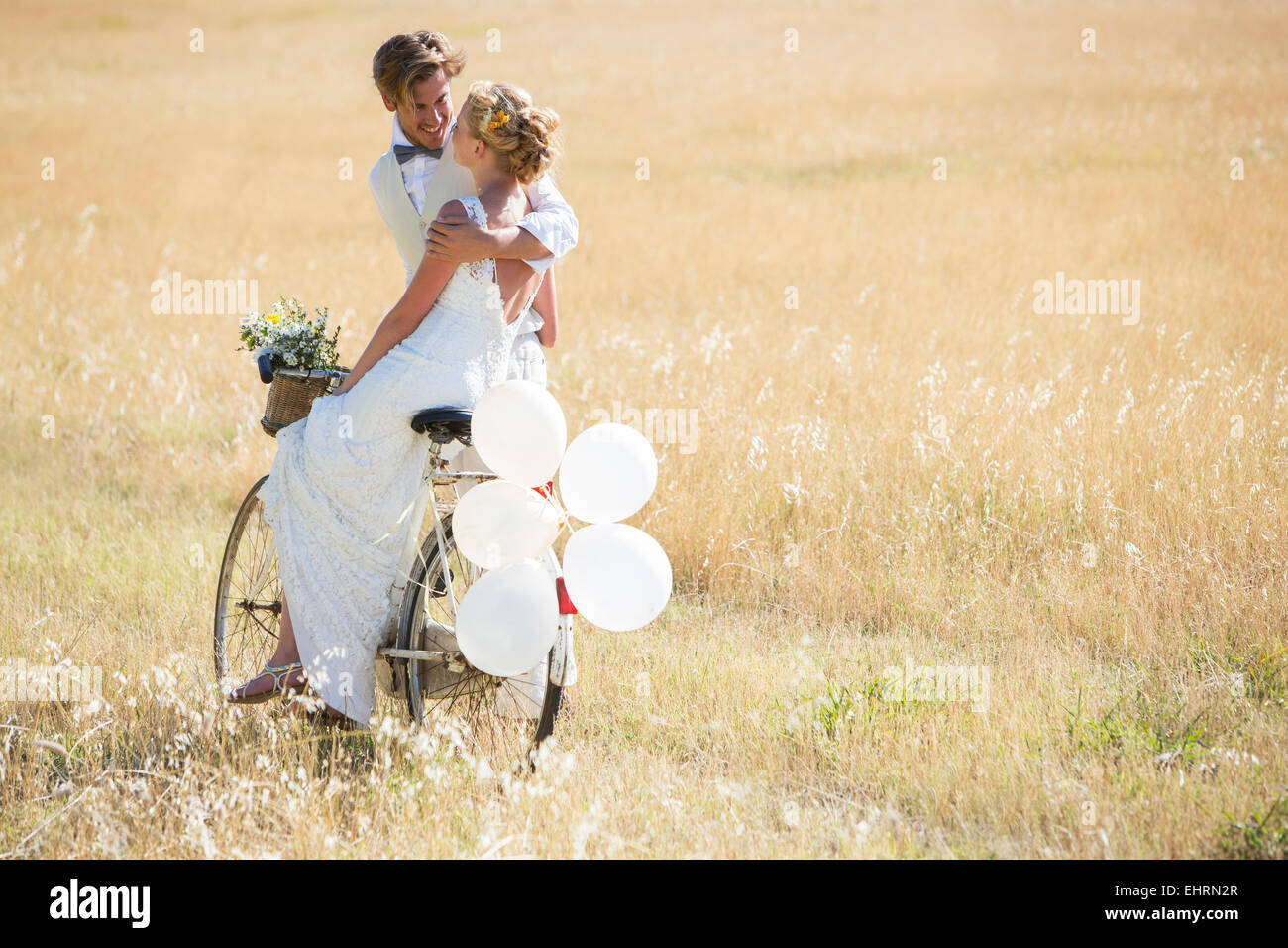 Bride and bridegroom riding bike with balloons attached - Stock Image