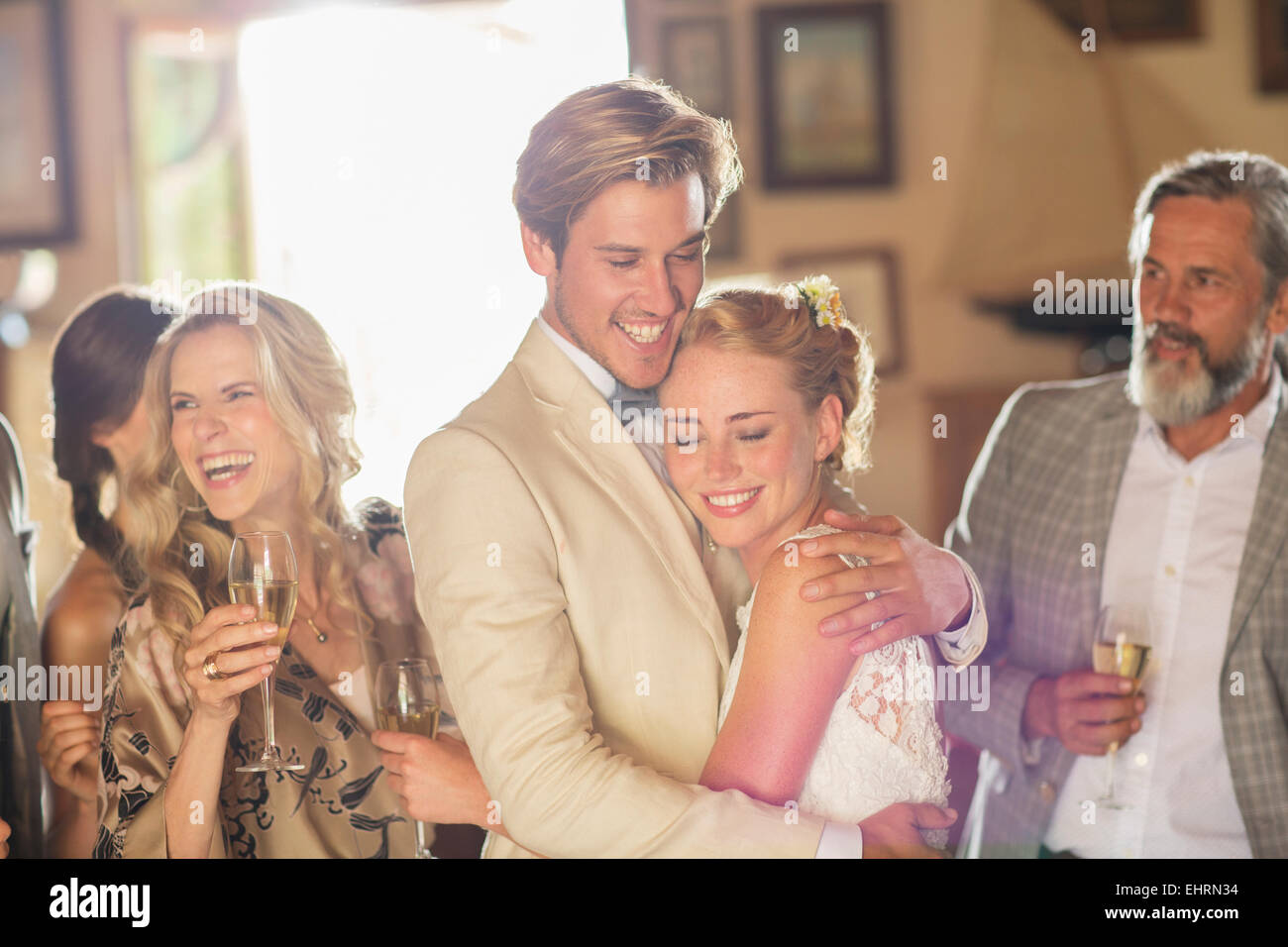 Young couple and guests at wedding reception in domestic room - Stock Image