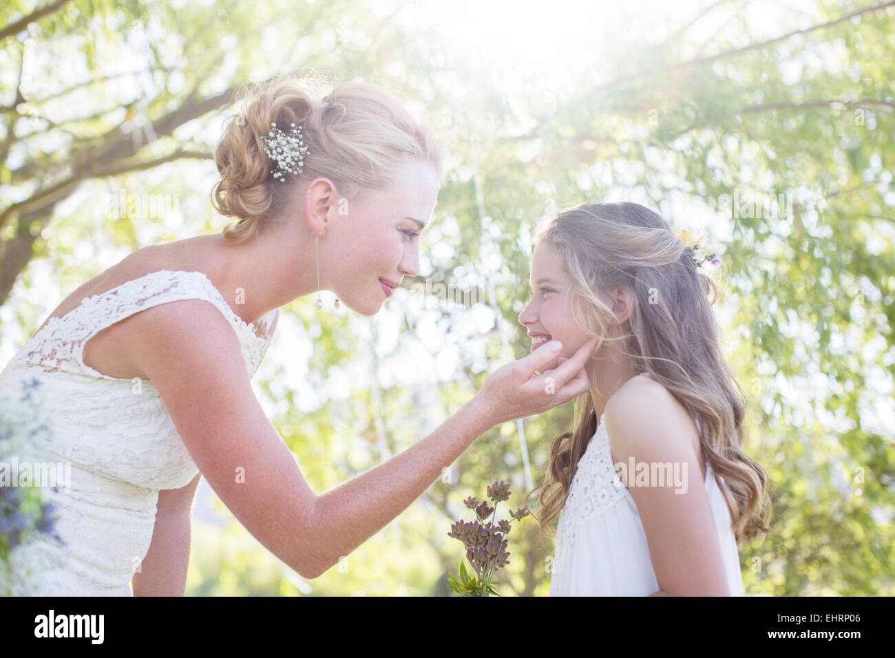 Bride and bridesmaid facing each other in domestic garden during wedding reception Stock Photo