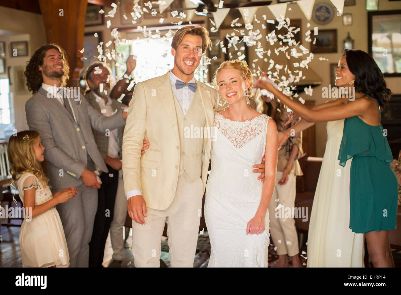Portrait of smiling young couple standing in falling confetti during wedding reception Stock Photo