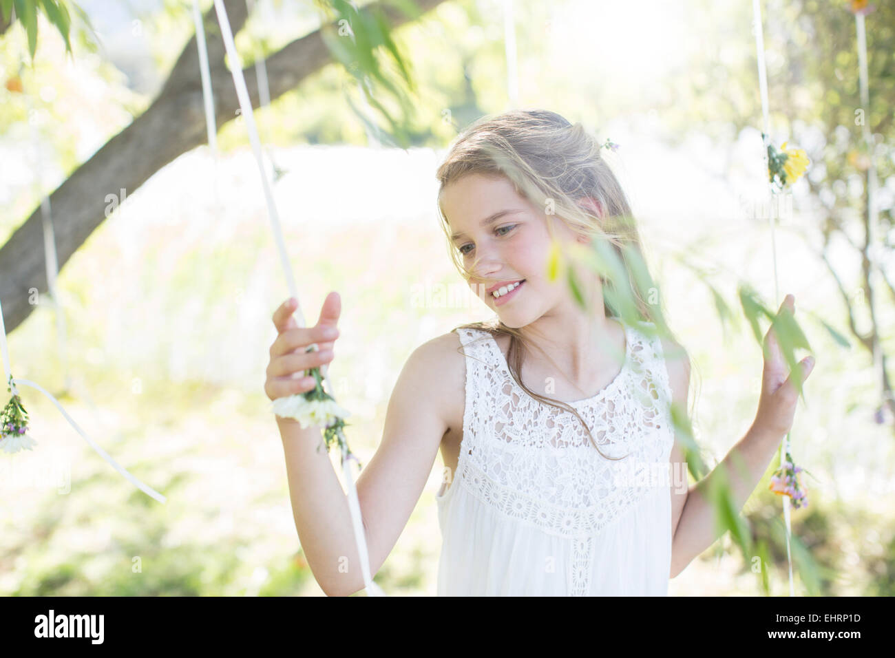 Smiling bridesmaid playing with decorations in domestic garden during wedding reception - Stock Image