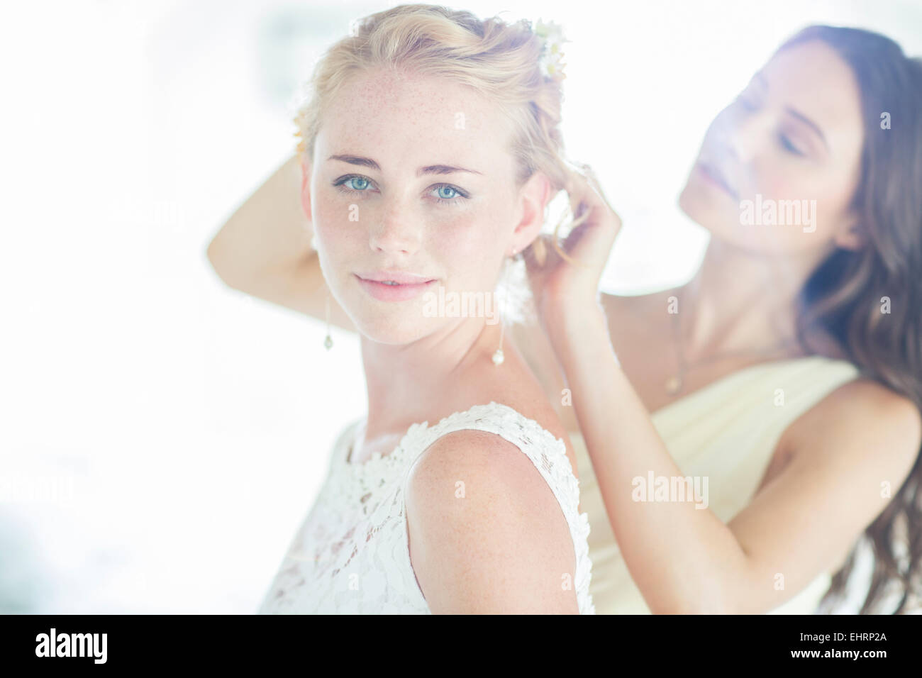 Bridesmaid helping bride with hairstyle in domestic room Stock Photo