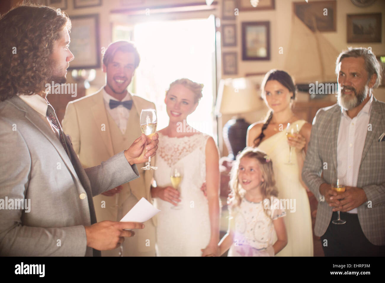 Best man toasting with champagne and giving speech during wedding reception in domestic room - Stock Image