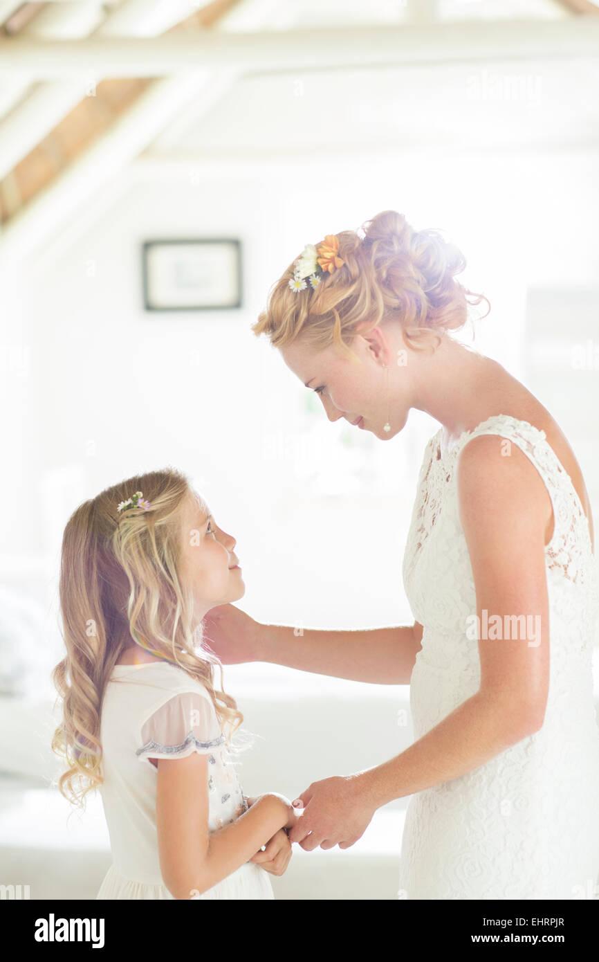Bride talking to bridesmaid in domestic room - Stock Image