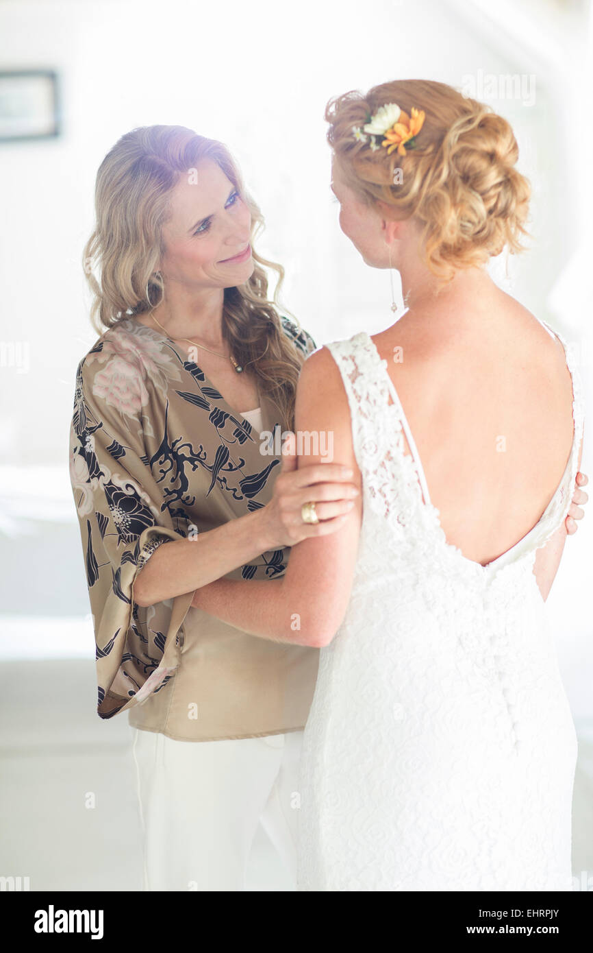 Matron of honor and bride talking in domestic room - Stock Image
