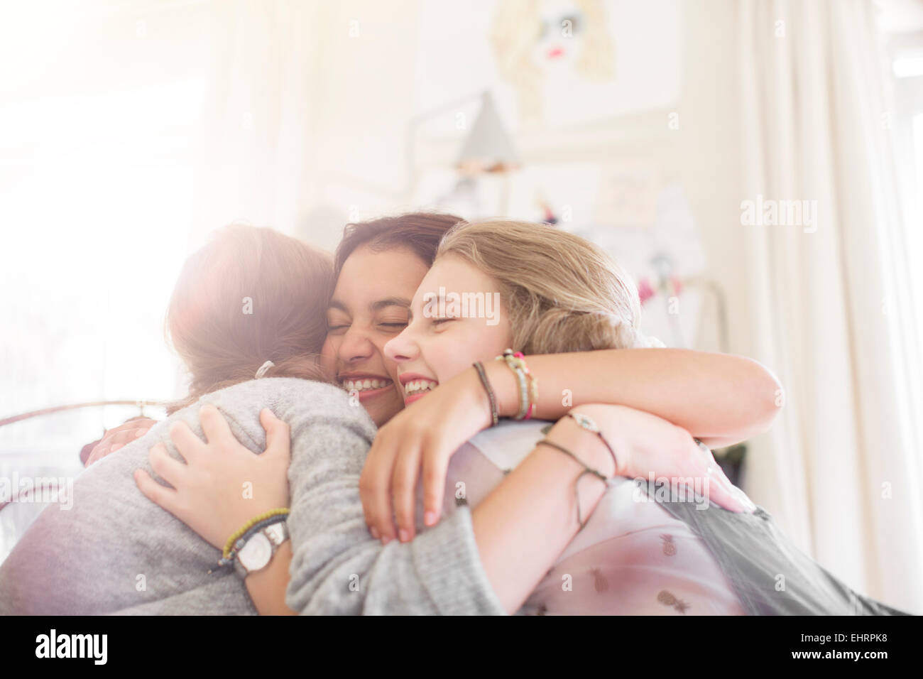 Three teenage girls embracing at home - Stock Image