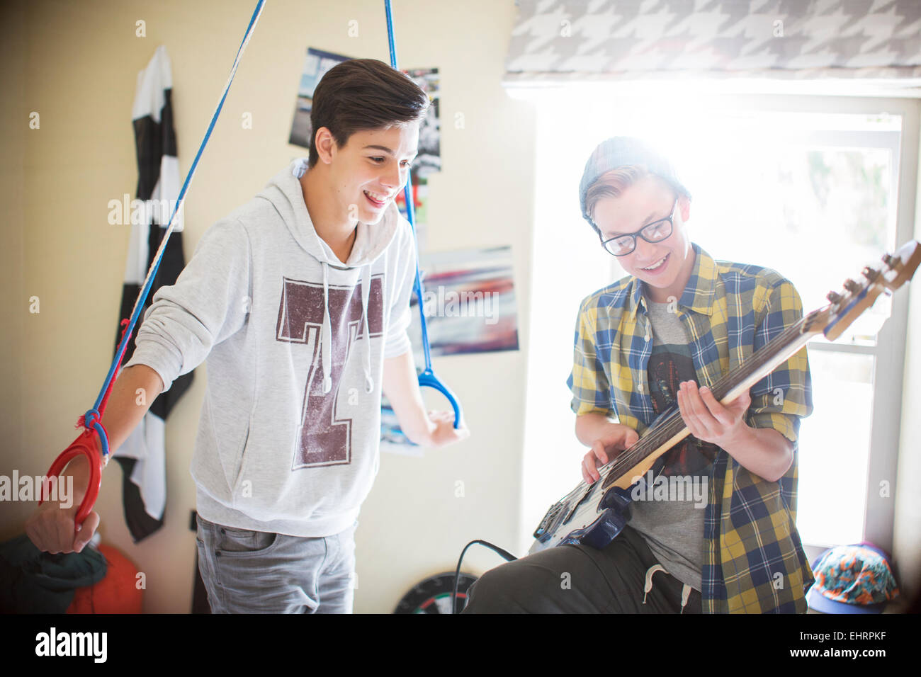 Two teenage boys having fun and playing electric guitar in room - Stock Image