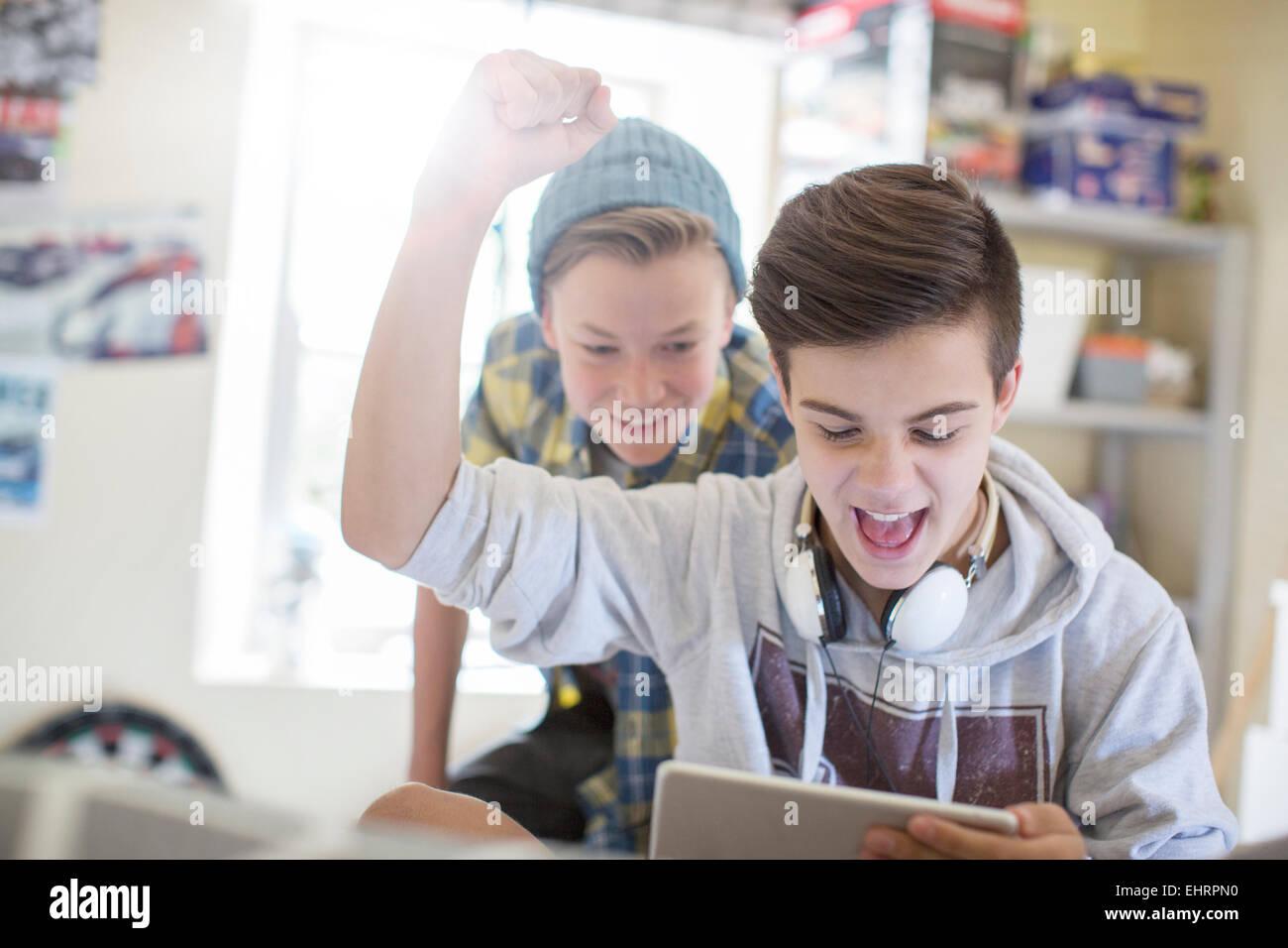 Two teenage boys having fun while using digital tablet - Stock Image