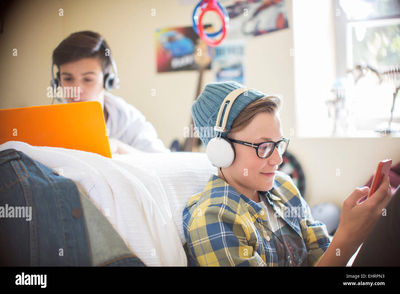 Two teenage boys using electronic devices in room - Stock Image