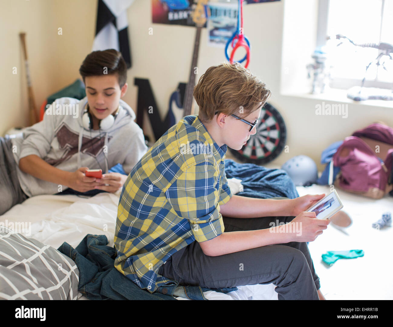 Two teenage boys using digital devices in room - Stock Image