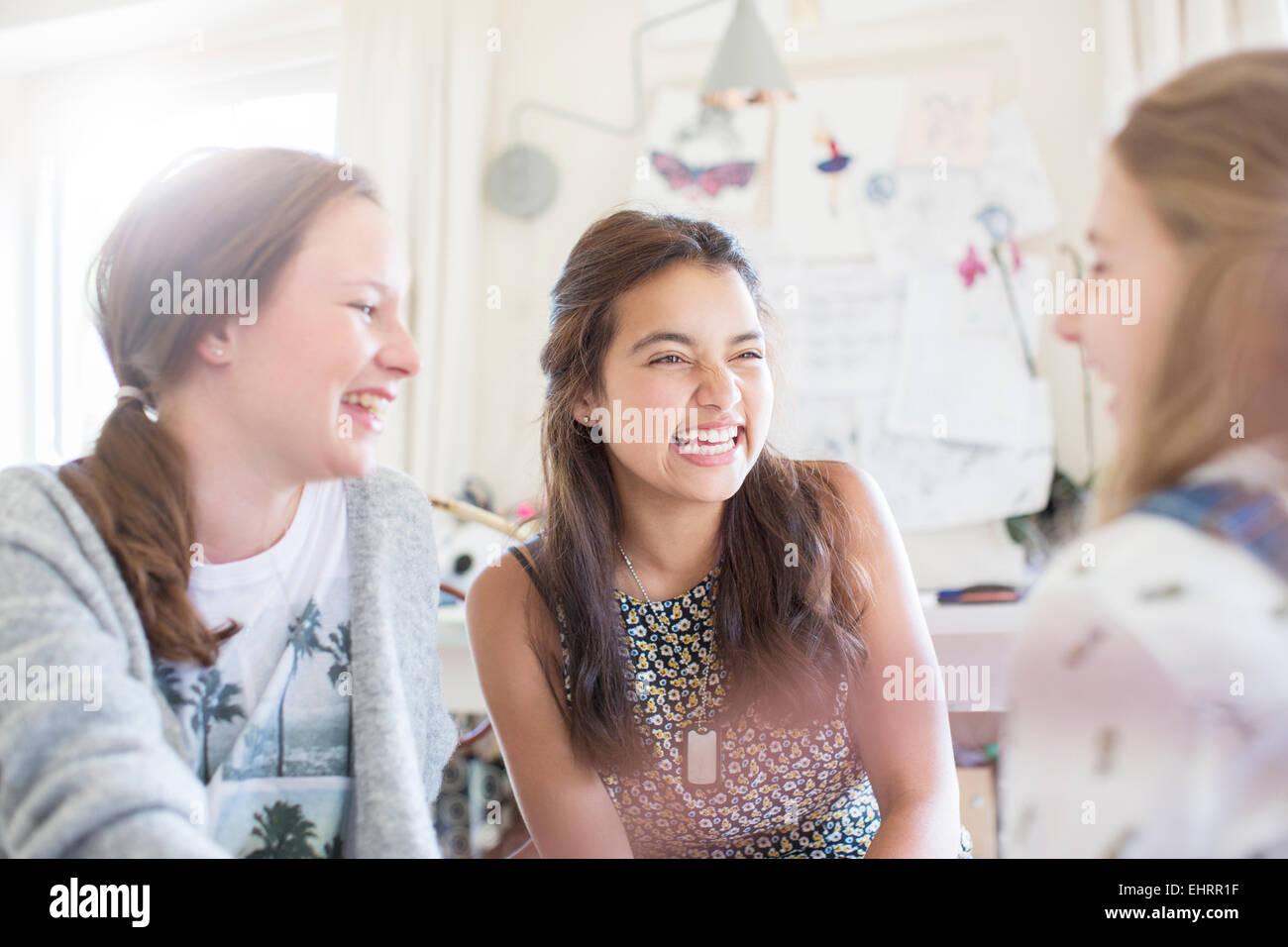 Three teenage girls laughing in room - Stock Image