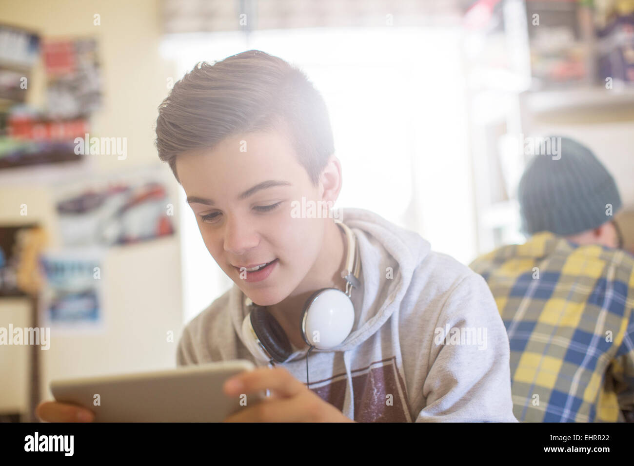 Two teenage boys sitting in room and using electronic devices - Stock Image