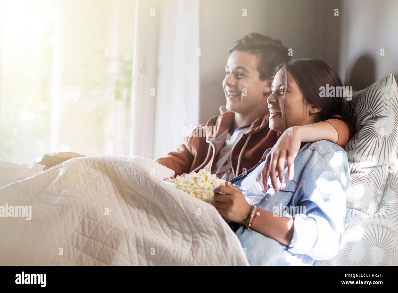 Teenage couple lying in bed and watching tv - Stock Image